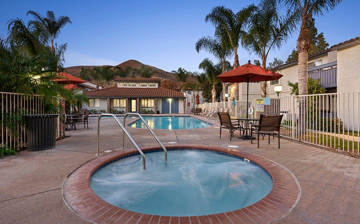 Circular hot tub near pool in the evening in front of hill at Wood Ranch, apartments in Simi Valley