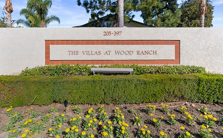 Placard for community in front of hedge and flowers at Wood Ranch, apartments in Simi Valley