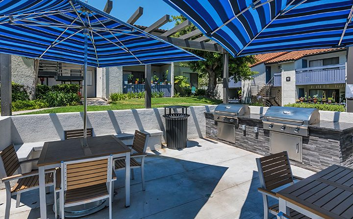 Chairs and tables under blue umbrellas on clear day at Wood Ranch, apartments in Simi Valley