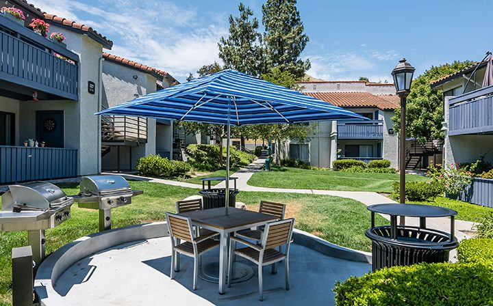 BBQ grills next to table under blue umbrella by grassy area at Wood Ranch, Simi Valley apartments
