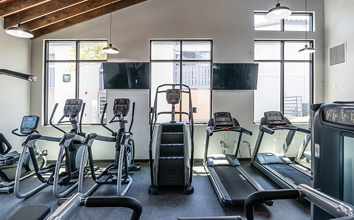 Cardio machines in front of TVs and windows at Wood Ranch, Simi Valley apartments