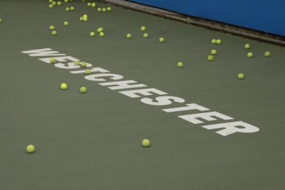 Green tennis court with Westchester lettering and many balls near Decron's Playa del Rey apartments