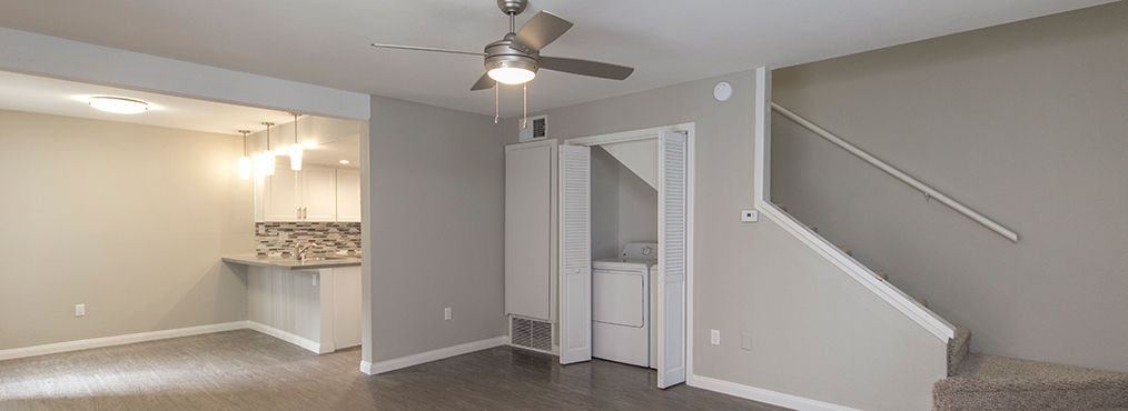 Unfurnished living room with in-unit washer and dryer at Decron's South Coast apartments