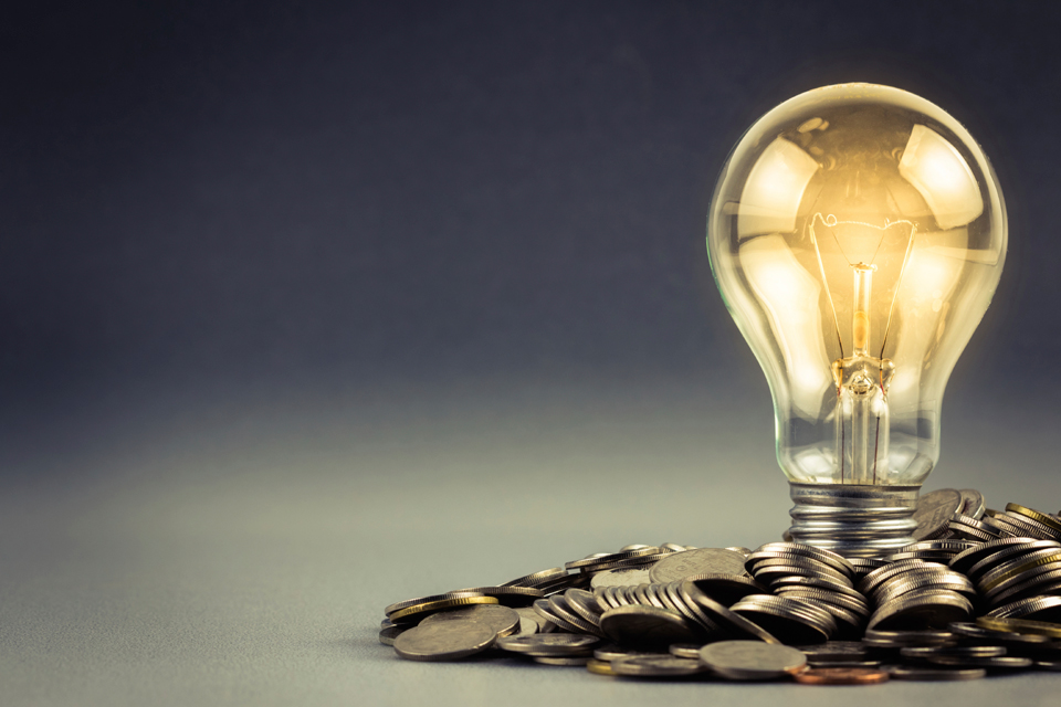 A bright lightbulb in a pile of coins