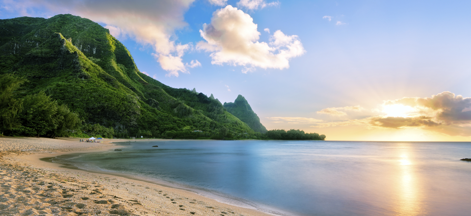Hawaiian cove beach at sunrise with green hills in background and sun reflected in water