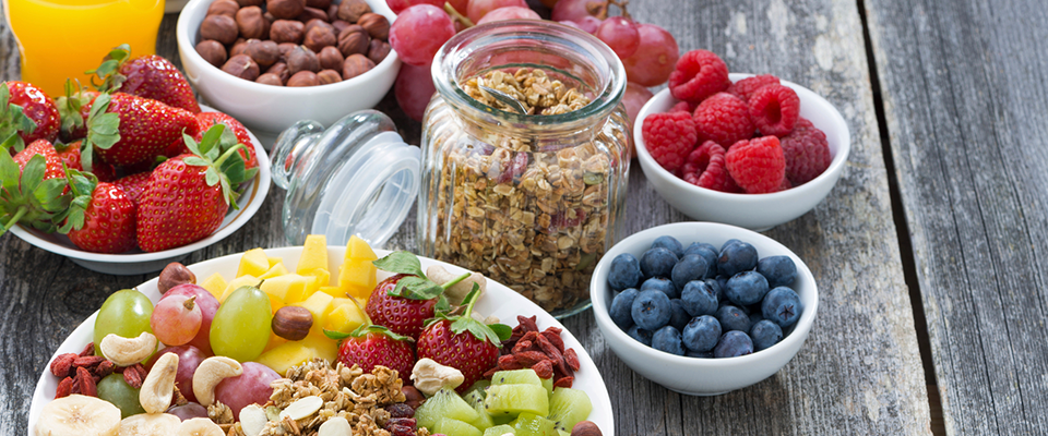 Healthy breakfast bowl fixings like fruit and nuts on a patio table