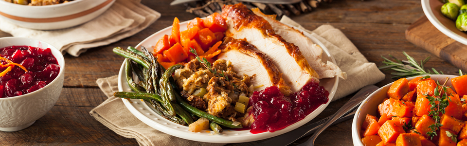 A plate filled with turkey, stuffing, and cranberry sauce
