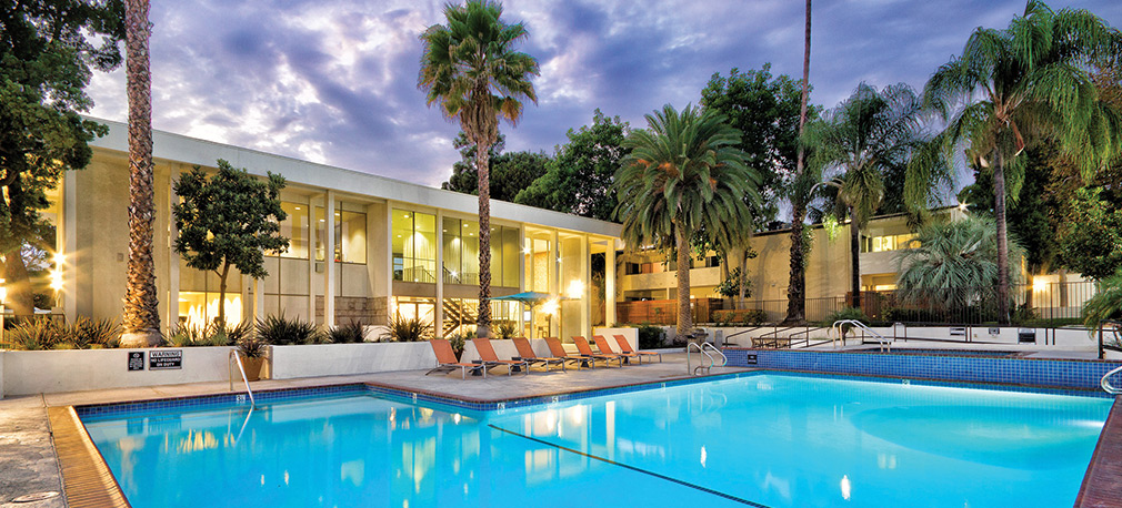 Cloudy evening and large resort-style pool on at one of Decron's apartments in Southern California