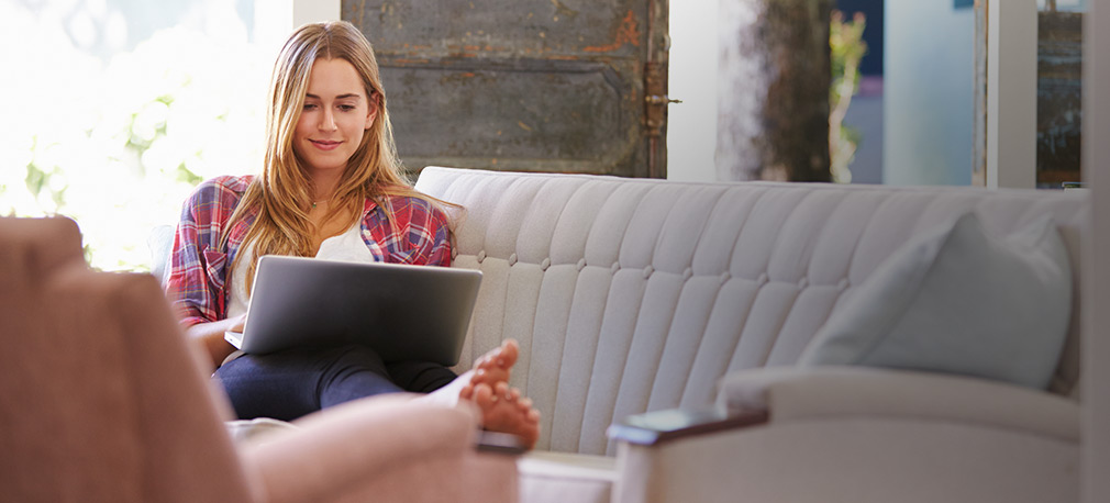 Woman smiling while sitting on couch on her laptop - pay rent and more online at Decron's portal!