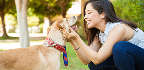 Woman smiling and petting her dog - discover Decron's pet-friendly apartments!