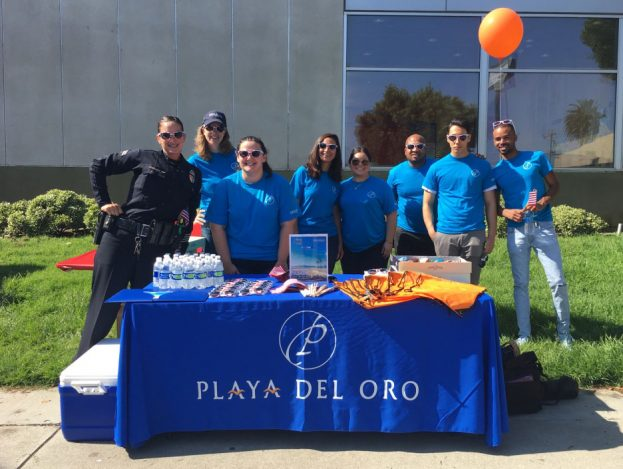 Decron Playa del Oro team and law enforcement individual in front of event booth outdoors