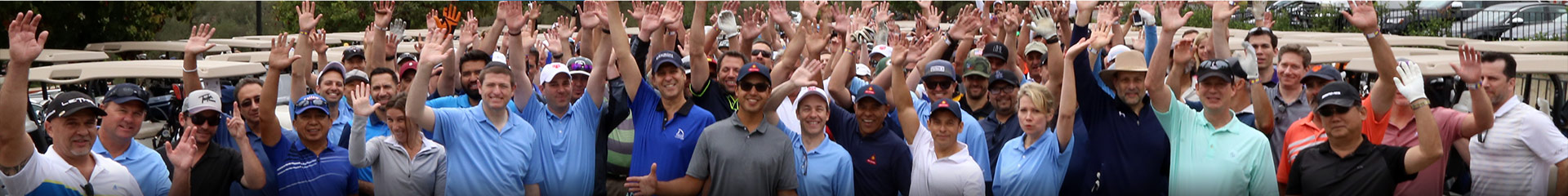 Decron team members posing for group photo with hands in the air at YULA golf benefit tournament