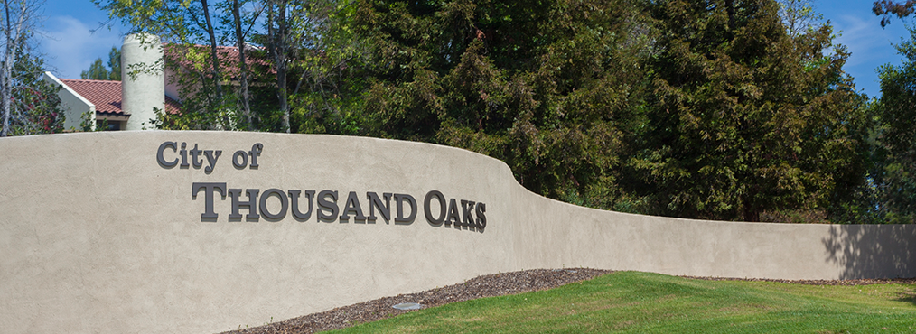 Sign on wall reading 'City of Thousand Oaks', near Decron's Thousand Oaks apartments
