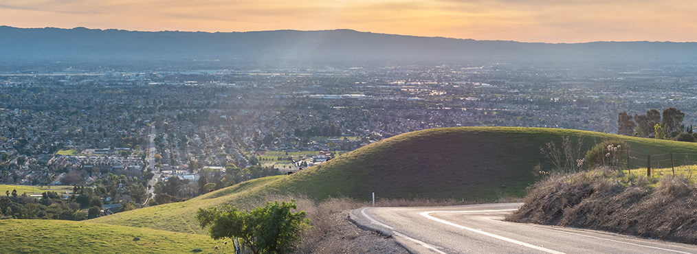 Winding hill road with view of city skyline, near where you can find Decron's San Jose apartments
