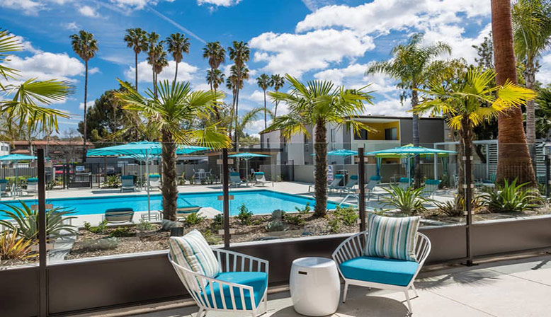 Large pool on sunny day with palm trees and umbrellas at The Retreat at Thousand Oaks apartments