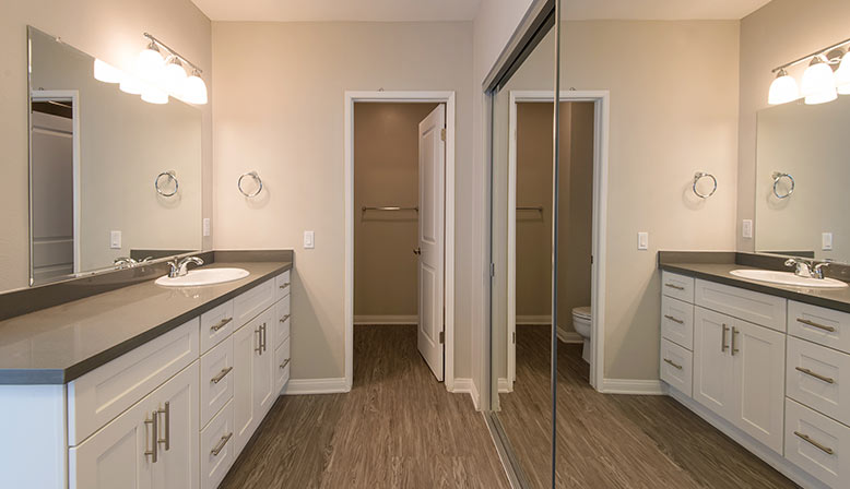 The Retreat at Thousand Oaks apartment bathroom with mirrored closet doors and sink cabinet space
