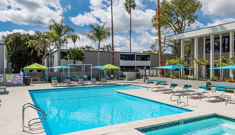 The Retreat at Thousand Oaks apartments sunny pool area with palm trees and umbrella shaded seating