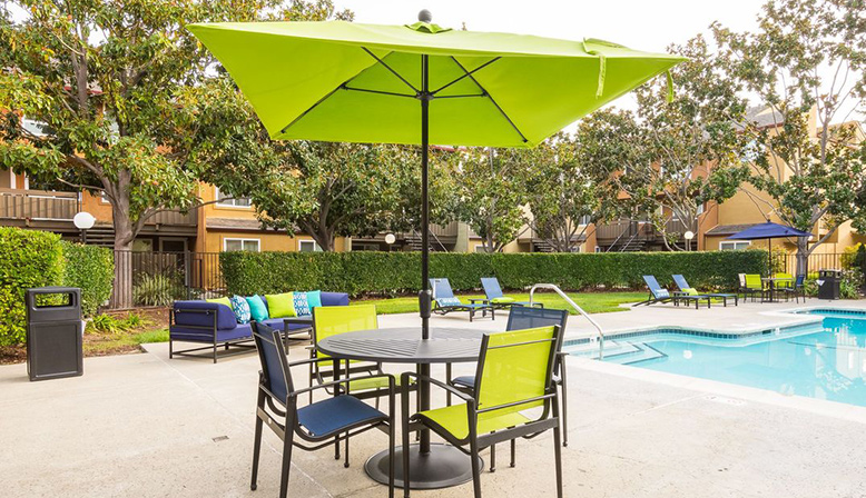 Pool seating and green umbrella at Fremont apartment community Rancho Luna Sol