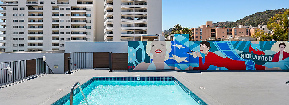Rooftop pool with view and mural at The Ruby Hollywood