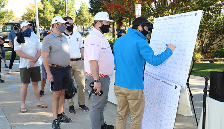 Attendees signing up at the 11th Annual Golf Tournament Benefiting YULA