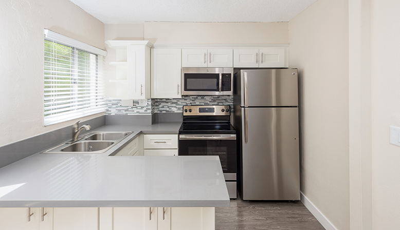 Corner kitchen with white cabinets at Playa Pacifica, Los Angeles apartments in Playa del Rey