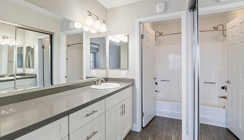 Bathroom hallway with cabinets and mirror closet doors at The Reserve at Carlsbad apartments