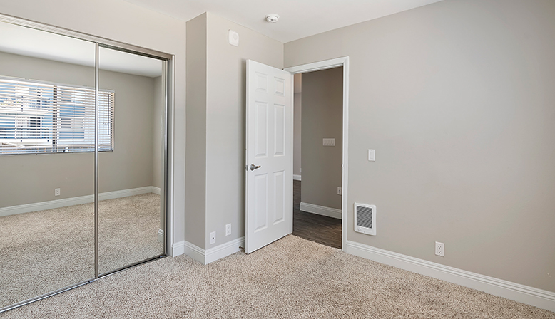 Unfurnished bedroom with mirrored closet doors at The Reserve at Carlsbad apartments
