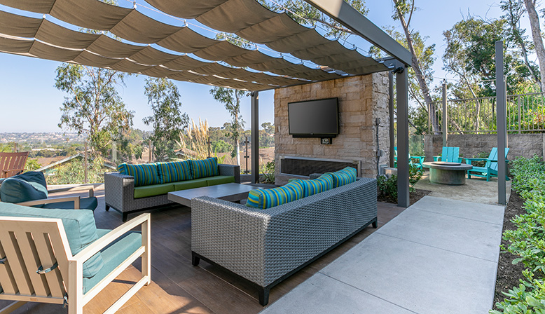 Lounge area with television outdoors near pool area at The Reserve at Carlsbad apartments