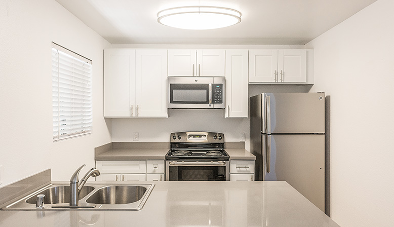 Bright kitchen with white walls, range, microwave, and stove at The Reserve at Carlsbad apartments