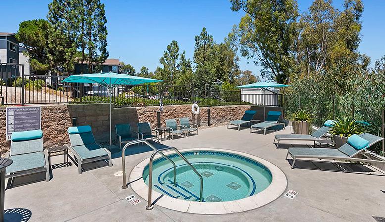 Small circular hot tub spa with outdoor seating and umbrella at The Reserve at Carlsbad apartments