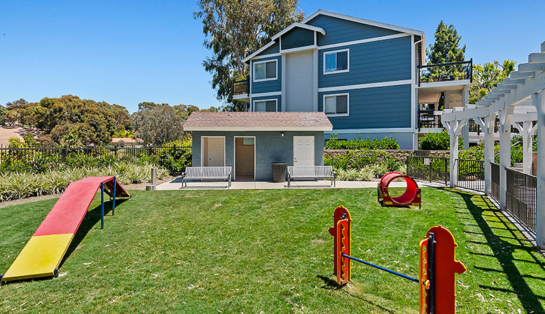 Grassy outdoor playground and dog park at The Reserve at Carlsbad apartments