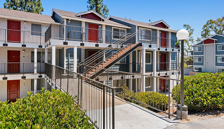 Exterior stairs to units with red doors at The Reserve at Carlsbad apartments