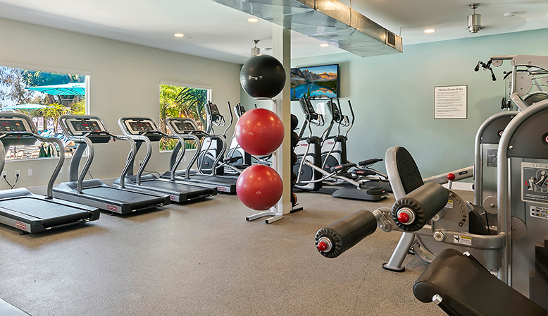 Fitness center with treadmills, bike machines and television at The Reserve at Carlsbad apartments