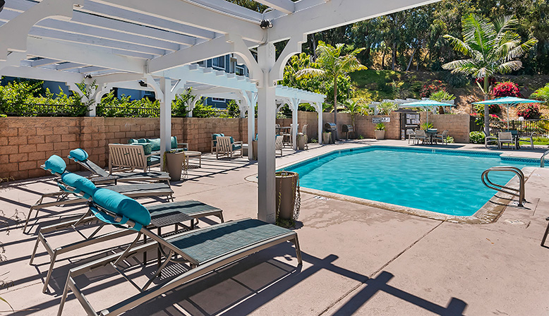 Large pool on sunny day with seating and overhead trellis at The Reserve at Carlsbad apartments