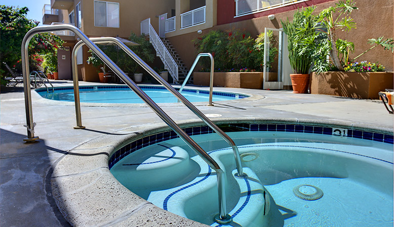 Hot tub next to pool on sunny day at Marlon Manor, Hollywood apartments in Los Angeles