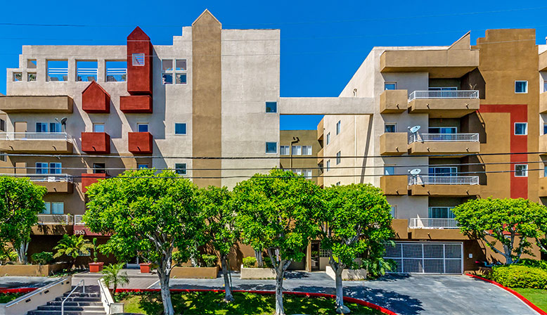 Streetside view of the Hollywood apartments community The Joshua, with red painted wall accents