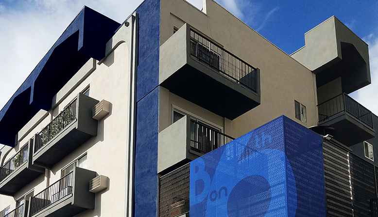 Streetside view of the Bay on 6th community, Santa Monica apartments with blue accents