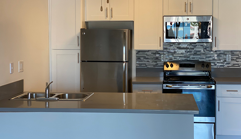 Unfurnished kitchen with brown cabinets at the Bay on 6th community, apartments in Santa Monica