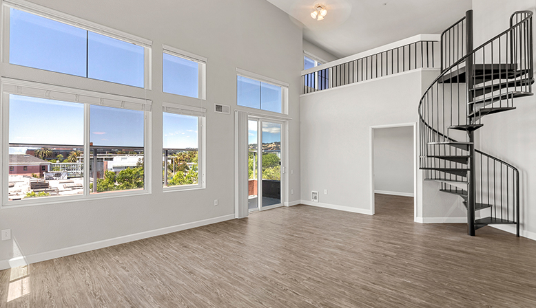 Living room with stairs in the 2x2 Marina Loft floor plan at the Bridge at Emeryville apartments