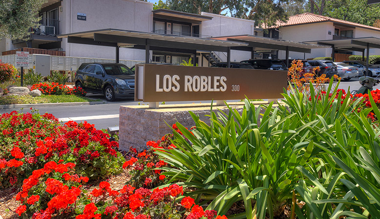 Rose bush in front of the sign and parking lot for Los Robles, apartments in Thousand Oaks