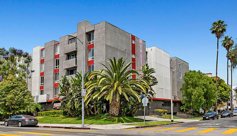 Streetside view of Media Towers, Hollywood apartments in Los Angeles with red wall accents