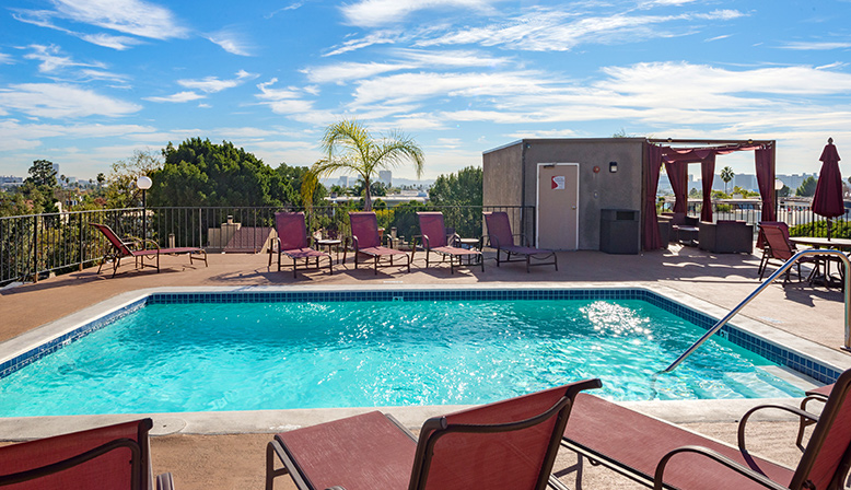 Aqua rooftop pool with red chairs at Villa Esther, Los Angeles apartments in West Hollywood