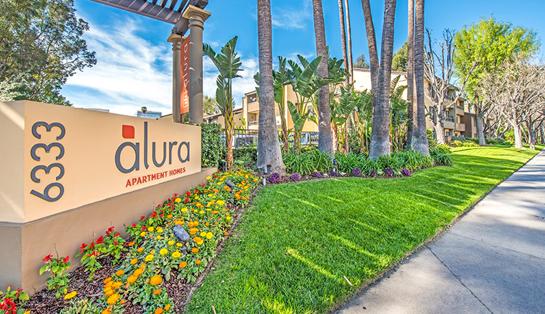 Exterior view of entrance to Woodland Hills apartments community Alura with sign and foliage